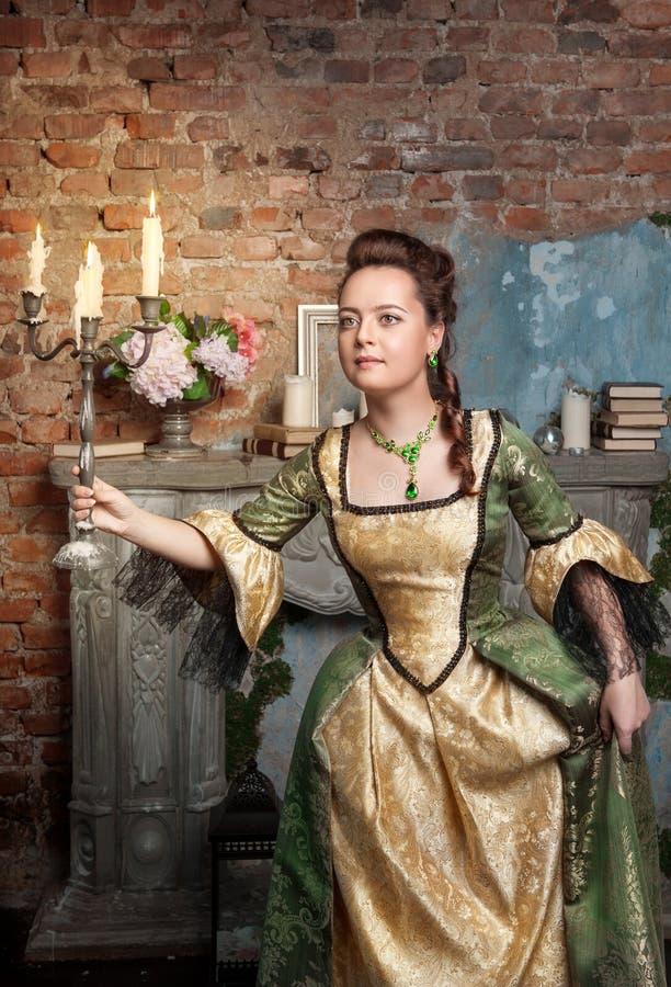 Mulher bonita no vestido medieval com velas ardentes imagem de stock royalty free