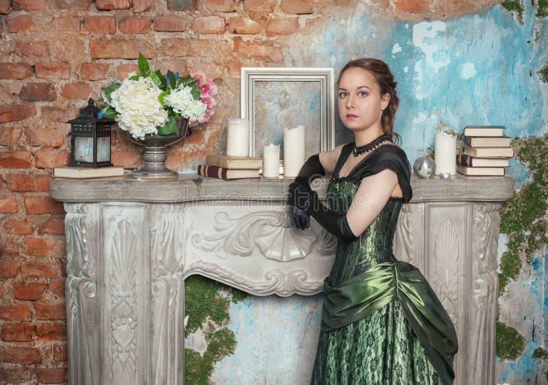 Mulher bonita no vestido medieval perto da chaminé imagens de stock