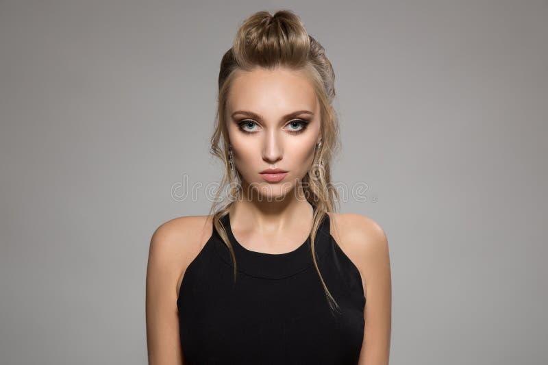Mulher bonita no vestido preto Penteado e composição brilhante fotografia de stock