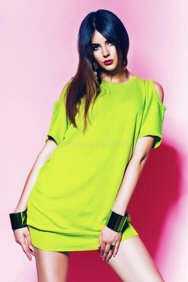 Mulher bonita no vestido verde de néon com bordos cor-de-rosa imagem de stock