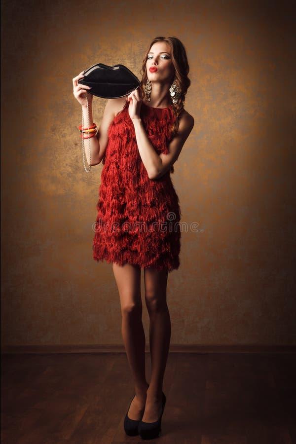a mulher bonita no vestido vermelho com bordos dá forma à bolsa fotos de stock