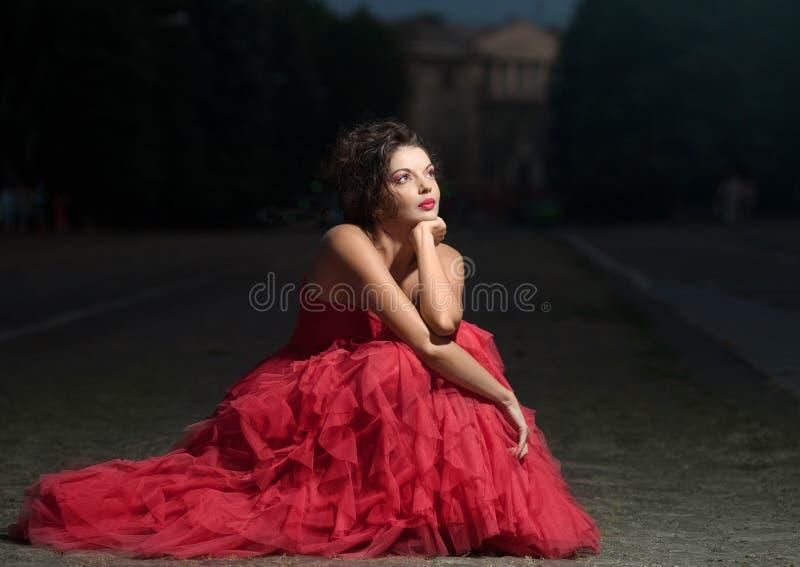 Mulher bonita no vestido vermelho no por do sol fotografia de stock royalty free