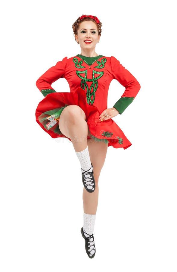 Mulher bonita no vestido vermelho para o salto irlandês da dança isolado fotografia de stock royalty free