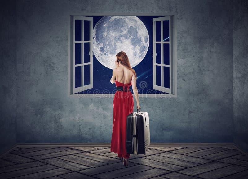 Mulher bonita no vestido vermelho que anda à janela aberta com lua fotografia de stock royalty free