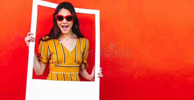 Mulher bonita nos óculos de sol com quadro vazio da foto imagem de stock