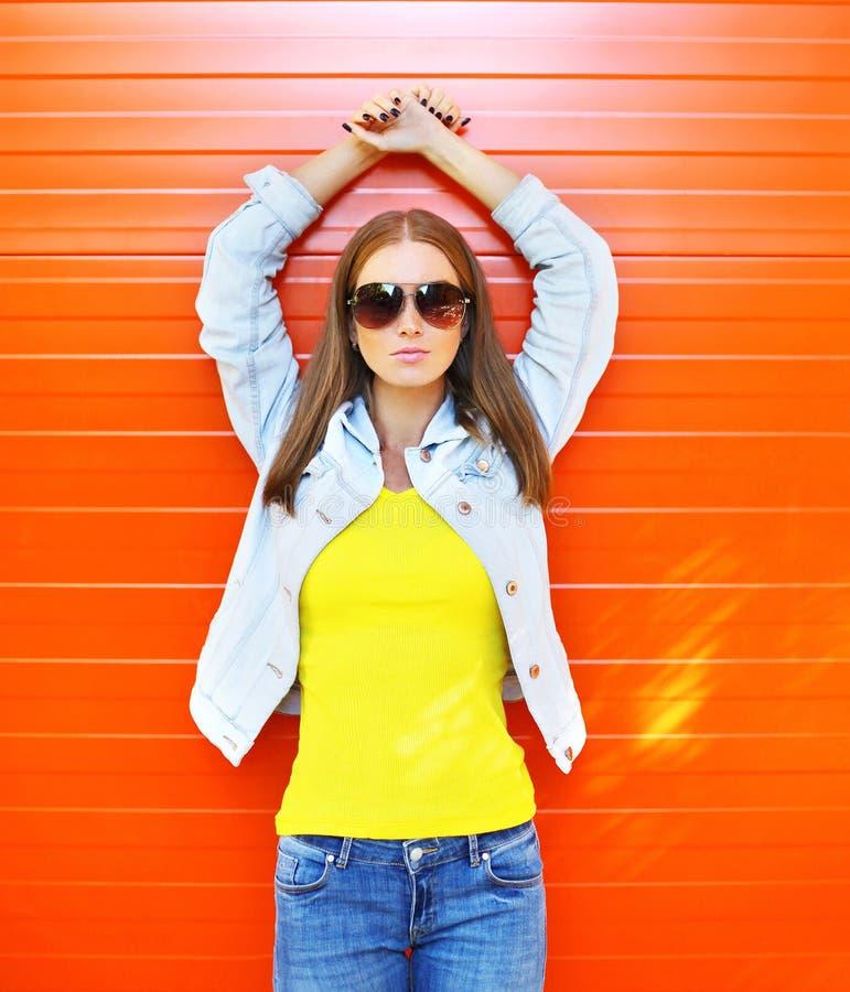 Mulher bonita nos óculos de sol e nas calças de brim sobre a laranja imagens de stock