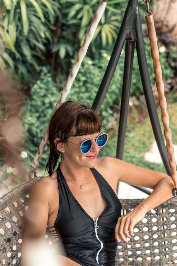 Mulher bonita nos óculos de sol que relaxam na espreguiçadeira na cadeira de sala de estar do sofá da cama do sol em feriados Fér fotografia de stock royalty free