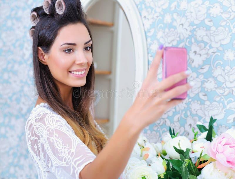 Mulher bonita nos encrespadores de cabelo que tomam a foto do selfie fotografia de stock royalty free