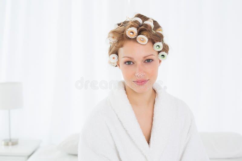 Mulher bonita nos encrespadores do roupão e de cabelo que sentam-se na cama imagem de stock royalty free