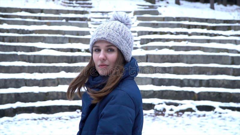 Mulher bonita nos sorrisos do chapéu do inverno que estão fora na neve na floresta com fundo nevado das escadas Retrato da imagem de stock