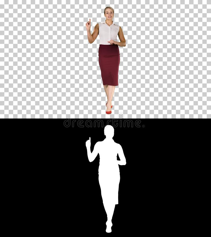 Mulher bonita nova alegre na roupa formal que anda, falando à câmera e apontando ao lado, Alpha Channel fotos de stock