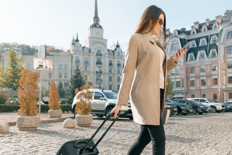 A mulher bonita nova anda ao longo da rua da cidade com mala de viagem e telefone celular do curso Sorriso moreno elegante da men fotos de stock royalty free
