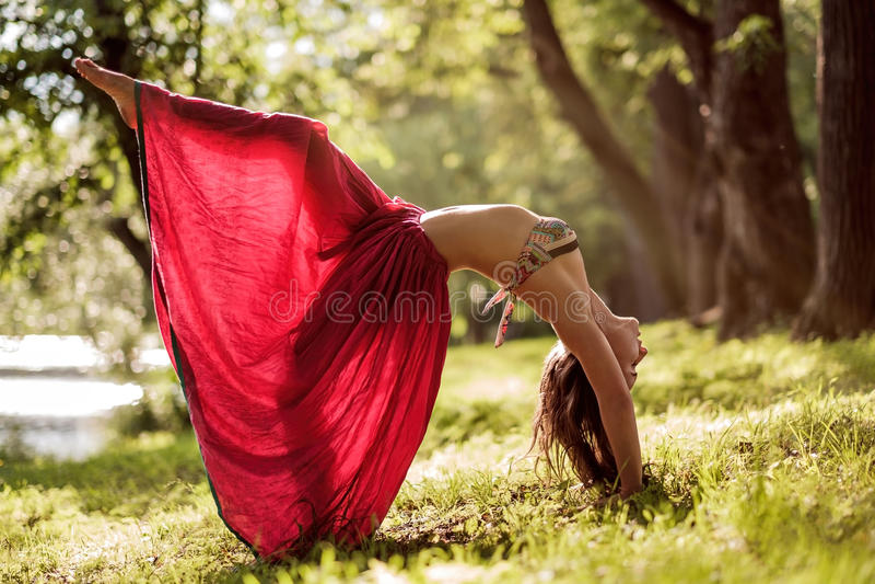 Mulher bonita nova apta que veste a saia vermelha que dá certo fora no parque no dia de verão, fazendo a pose da ponte da ioga fotografia de stock