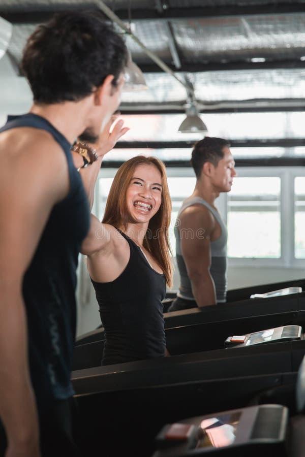 Mulher bonita nova asiática cinco altos ao exercitar no treadmi imagens de stock
