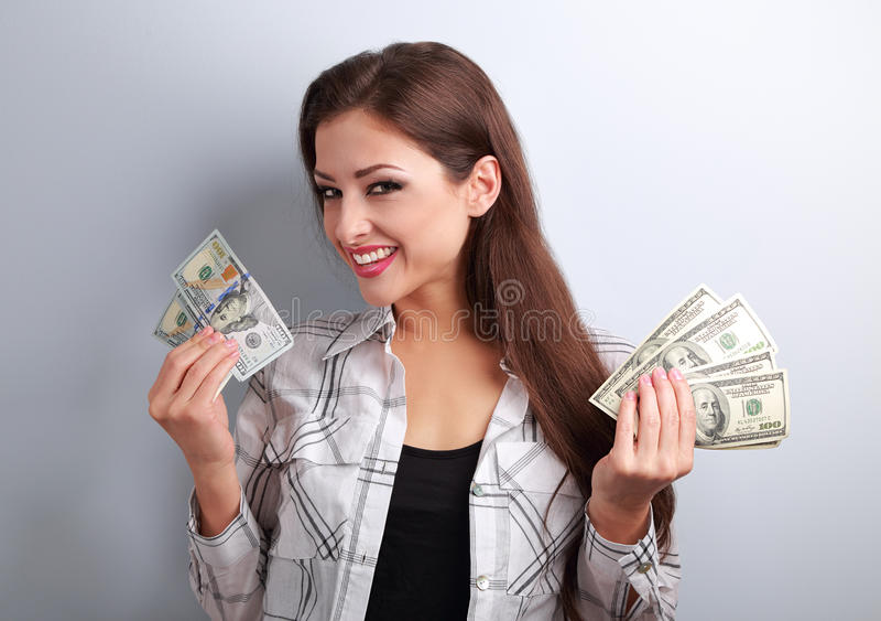 Mulher bonita nova bem sucedida que guarda dólares em duas mãos com fotografia de stock