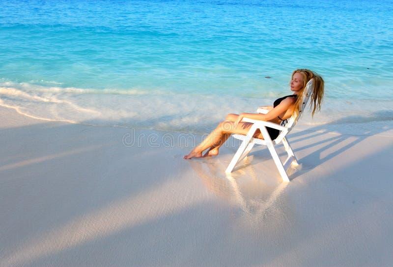 A mulher bonita nova bronzea-se na cadeira de praia, ele pôs no oceano fotografia de stock