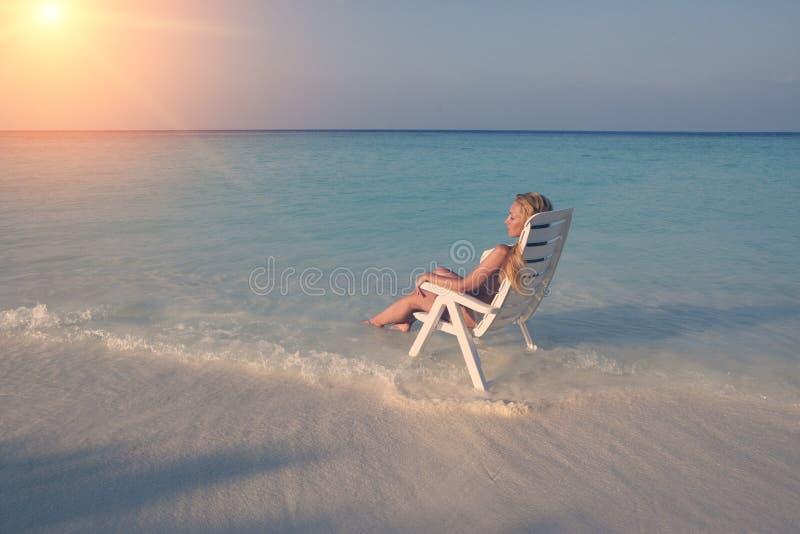 A mulher bonita nova bronzea-se na cadeira de praia no mar, tonificando imagens de stock royalty free