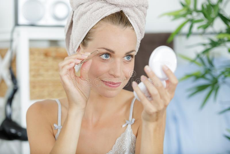 Mulher bonita nova com as sobrancelhas das formas de toalha fotos de stock