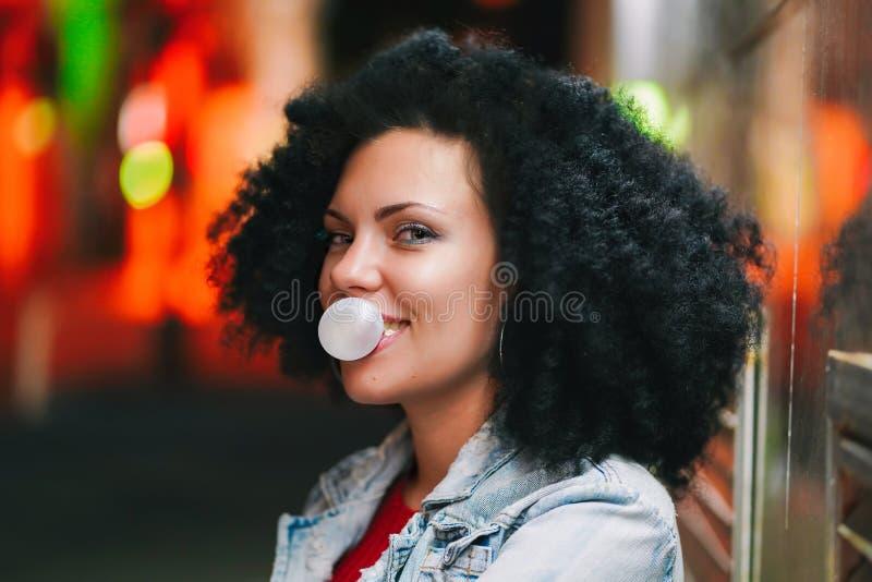 A mulher bonita nova com cabelo afro muito encaracolado infla uma bola da bolha da pastilha elástica branca na noite Menina na mo fotografia de stock royalty free
