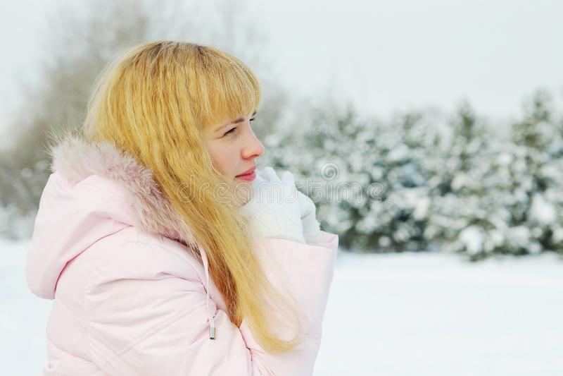Mulher bonita nova com cabelo dourado que admira a natureza no inverno imagem de stock royalty free