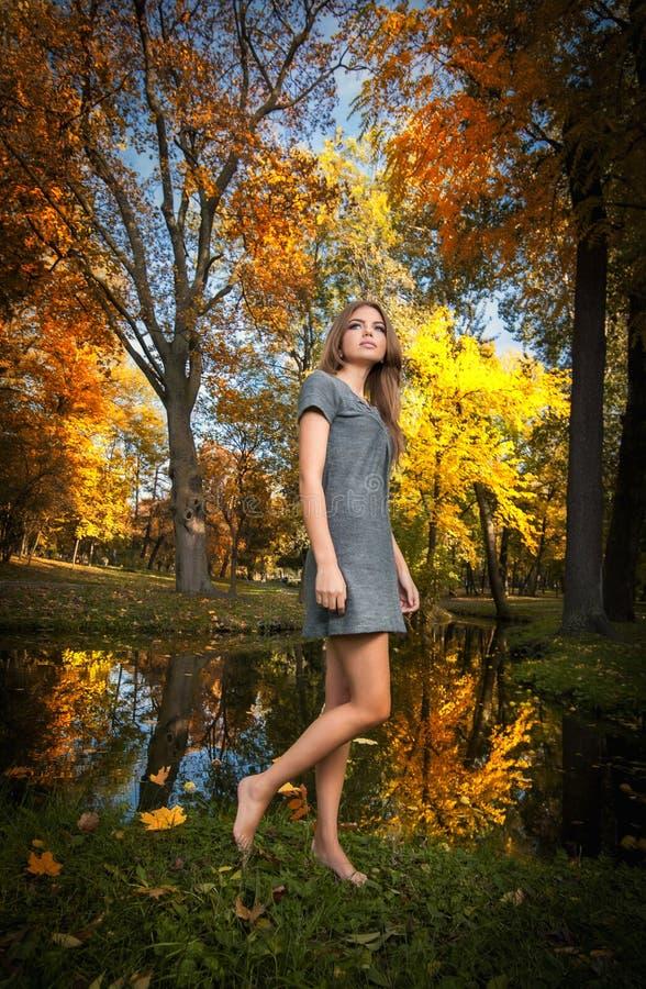 Mulher bonita nova com cabelo louro que passa o tempo no parque outonal. Louro sensual dos pés longos com passeio na floresta imagens de stock
