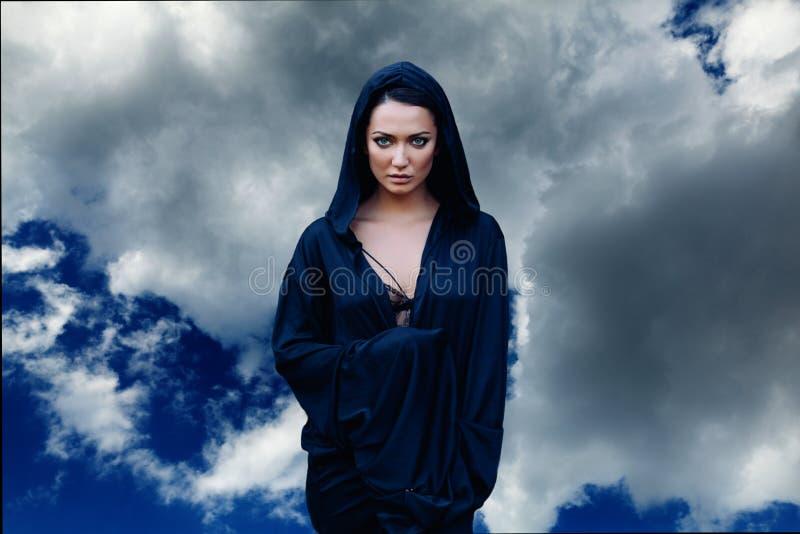 Mulher bonita nova com cabelo preto e no escuro - casaco azul com a capa no fundo do céu imagem de stock