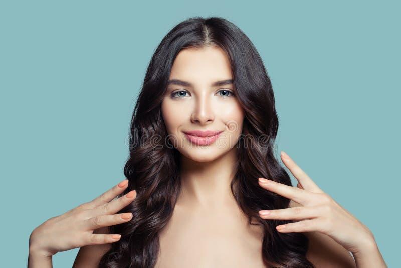 Mulher bonita nova com cabelo saudável longo e composição natural no fundo azul Menina moreno feliz, cuidados capilares fotografia de stock royalty free