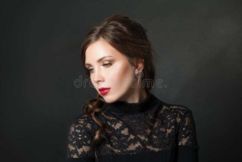 Mulher bonita nova com cabelo vermelho da composição dos bordos no fundo preto imagens de stock