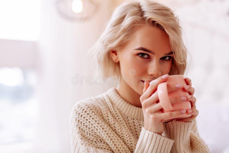 Mulher bonita nova com corte do prumo que aprecia o chá saboroso fotografia de stock royalty free
