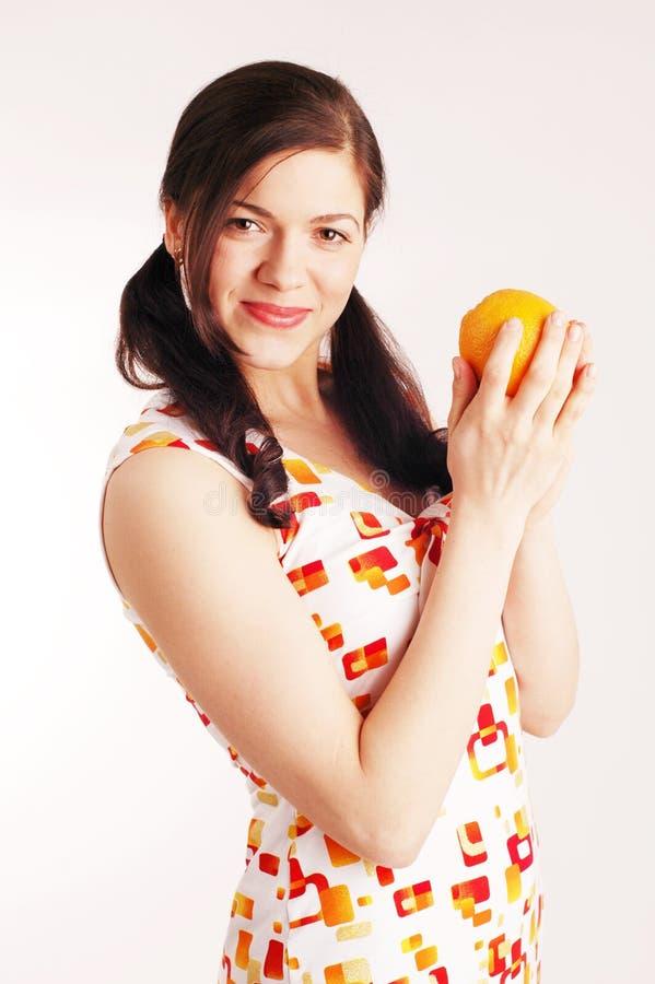 Mulher bonita nova com laranja foto de stock