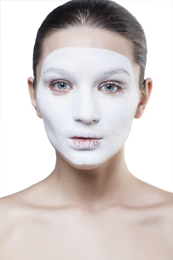 Mulher bonita nova com a máscara branca facial isolada foto de stock