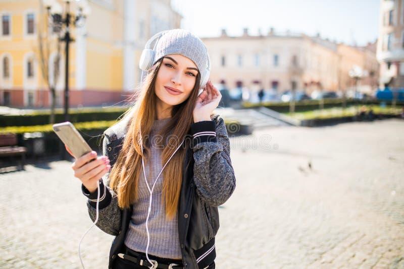 Mulher bonita nova com música de escuta do telefone esperto na cidade imagens de stock royalty free