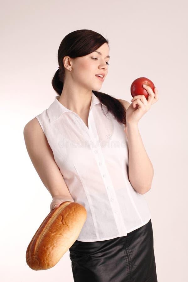 Mulher bonita nova com maçã e pão vermelhos foto de stock royalty free