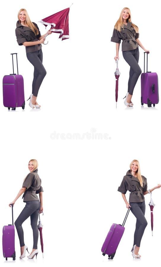 Mulher bonita nova com a mala de viagem e o guarda-chuva isolados no whi foto de stock
