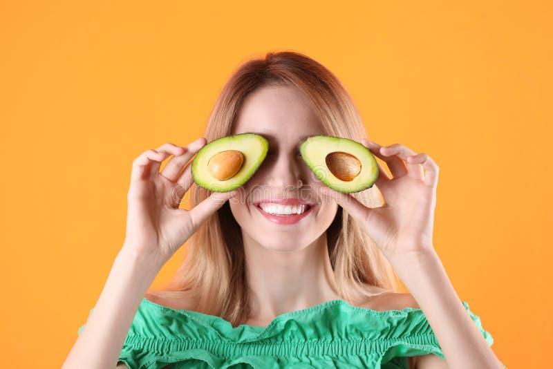 Mulher bonita nova com o abacate delicioso maduro no fundo da cor foto de stock
