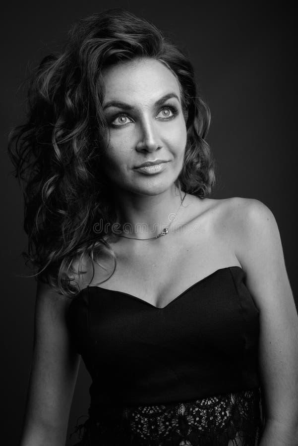 Mulher bonita nova com o cabelo encaracolado que levanta em preto e branco imagem de stock royalty free
