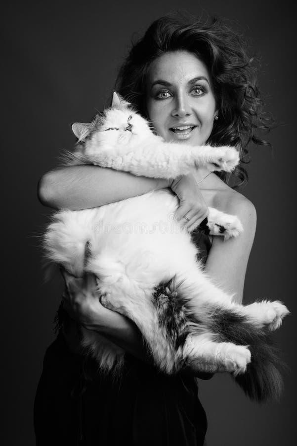 Mulher bonita nova com o cabelo encaracolado que levanta em preto e branco fotografia de stock royalty free