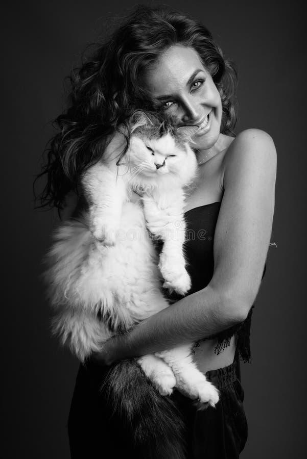 Mulher bonita nova com o cabelo encaracolado que levanta em preto e branco fotografia de stock
