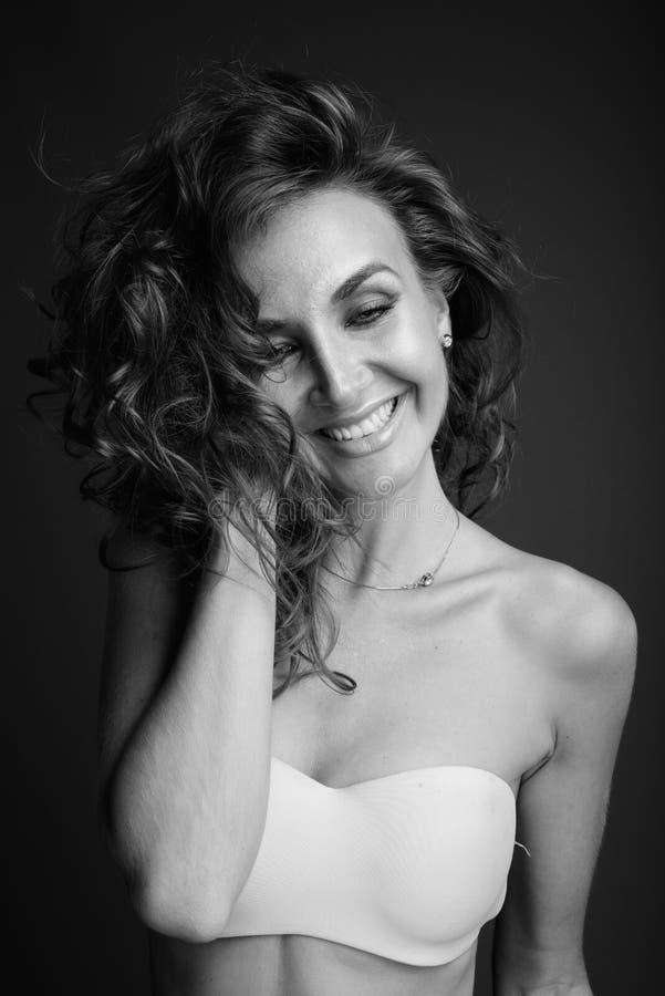 Mulher bonita nova com o cabelo encaracolado que levanta em preto e branco imagens de stock royalty free