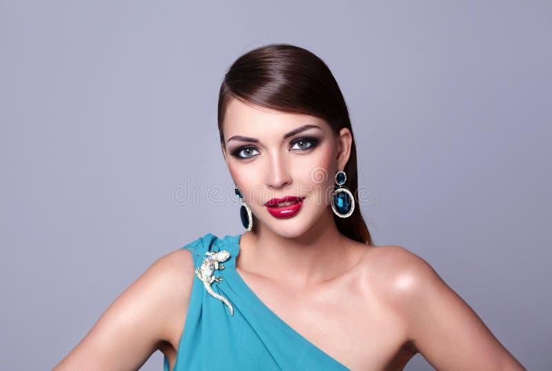 Mulher bonita nova com o cabelo longo que levanta no vestido de noite azul foto de stock royalty free