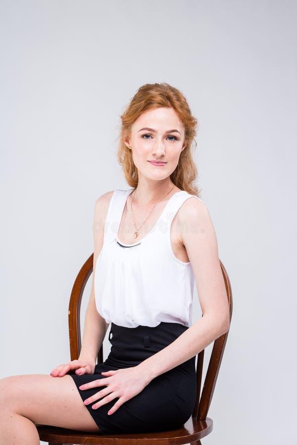 Mulher bonita nova com o cabelo vermelho, encaracolado longo que senta-se em uma cadeira de madeira em um fundo branco no estúdio imagens de stock