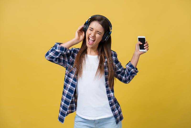 Mulher bonita nova com os fones de ouvido que dançam e que cantam isolados no fundo amarelo fotografia de stock royalty free