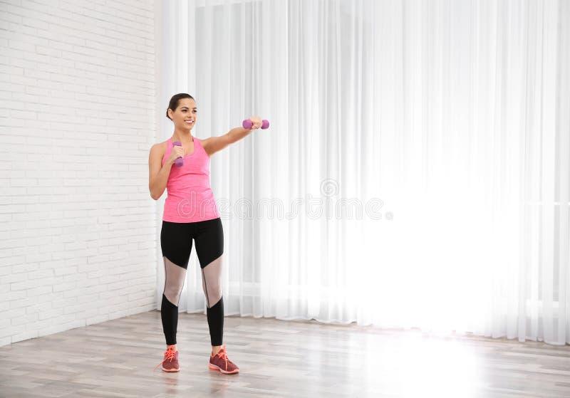 Mulher bonita nova com os pesos que fazem o exercício, espaço para o texto Exercício e aptidão imagens de stock