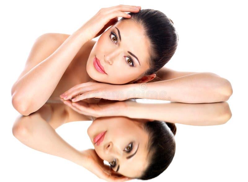 Mulher bonita nova com reflexões saudáveis da pele em um espelho foto de stock royalty free