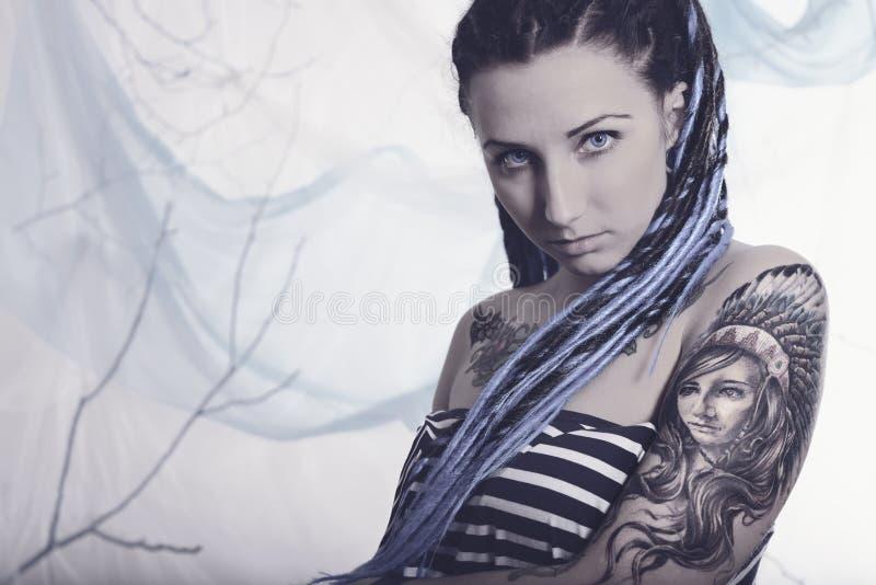 Mulher bonita nova com tatuagem e dreadlocks fotografia de stock royalty free