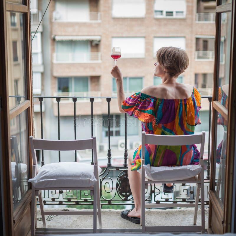 Mulher bonita nova com um vidro do vinho tinto à disposição, no t foto de stock royalty free