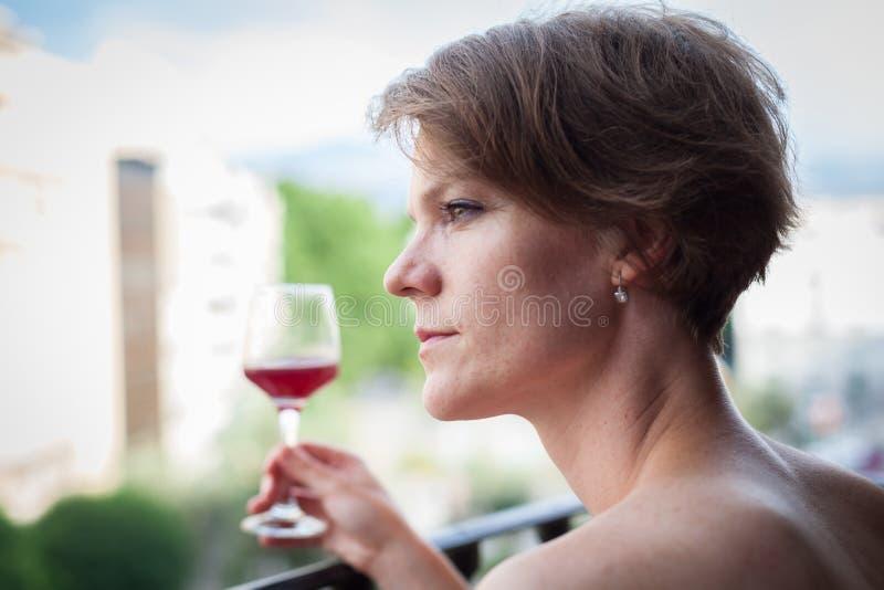 Mulher bonita nova com um vidro do vinho tinto à disposição, no t imagem de stock royalty free