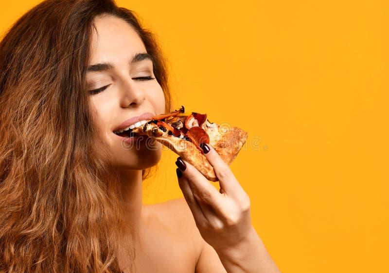 A mulher bonita nova come a fatia de pizza de pepperoni com olhos fechados que sorri no amarelo fotos de stock