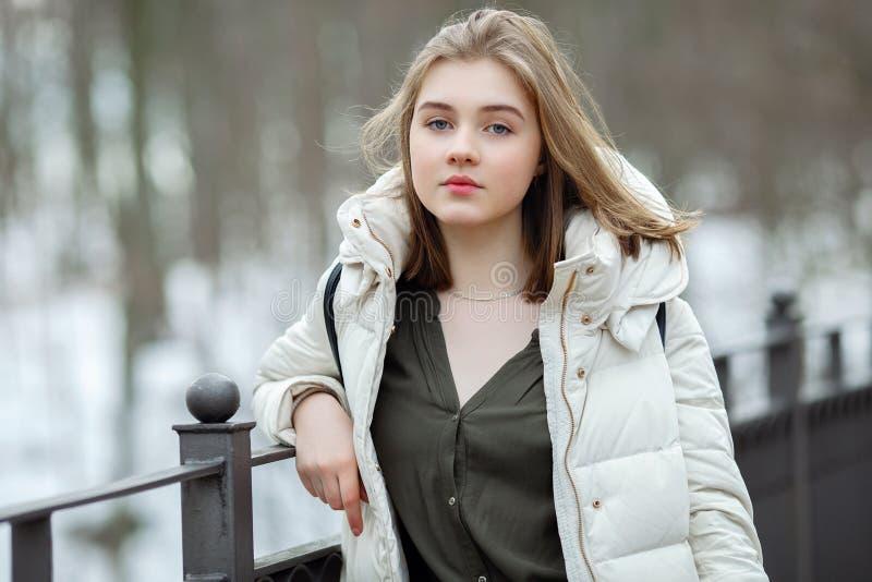 Mulher bonita nova da estação fria no revestimento branco com o cabelo bagunçado que levanta no retrato do conceito do estilo de  fotos de stock