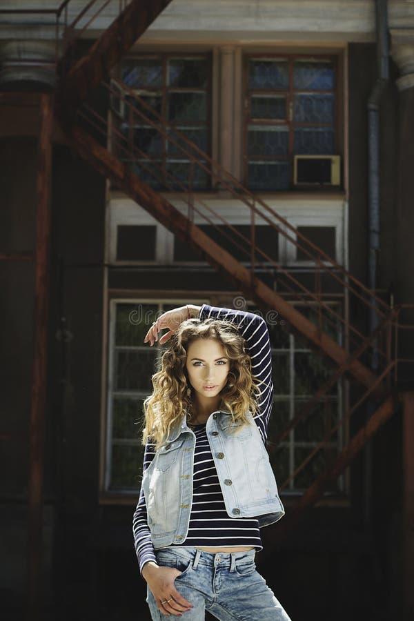 A mulher bonita nova da forma que veste calças de brim veste-se na luz do dia imagens de stock